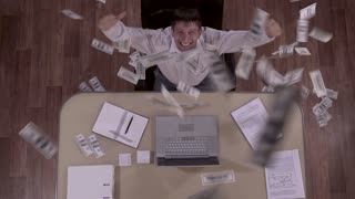 Down shot of happy excited businessman and a huge amount of banknotes falling down