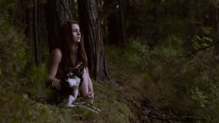 Enigmatic girl with her husky dog sitting near ravine in the wood