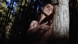 Enigmatic nude woman standing against a big tree in the rays of the sun