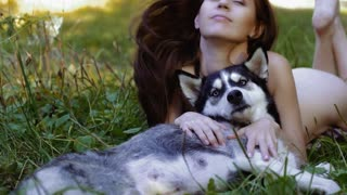 Enigmatic young woman lying with her dog on meadow gazes intently at something