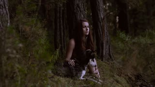 Enigmatic young woman sitting in the forest with beautiful dog and looking at the camera