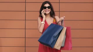 Excited young woman holding shopping bags and talking on the phone