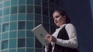 Fair-skinned attractive business woman working on the tablet outdoors