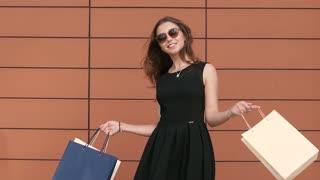 Fair-skinned beautiful girl turns shopping bags enjoying her purchases