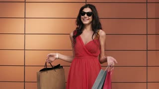 Fair-skinned young woman waves her shopping bags