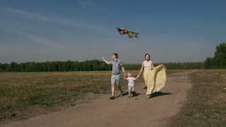 Family running in the field with kite on a bright summer day