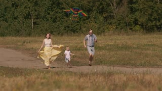 Family running together around the field flying a kite