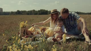 Family spending their weekend in nature. They sit in the meadow. Little son hug his toy, his mother embraces him