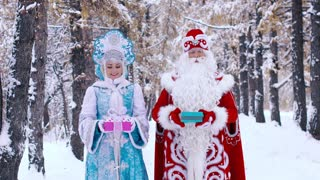 Father Frost and Snow Maiden coming close to the camera and show the gives to the camera
