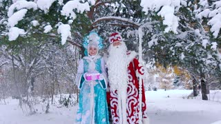 Father Frost and Snow Maiden standing under snow-covered tree