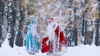 Father Frost picking up the bag with New Year gifts, and snowflake helping him