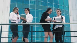 Four fair-skinned business women standing on terrace of office center and discussing their business