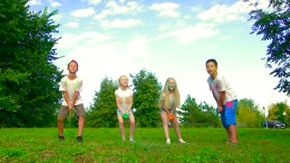Four kids in field throwing holy powder up to the air and having fun