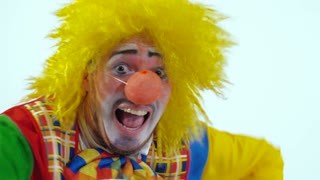 Funny clown in colorful costume running frightened toward camera. Close-up shot