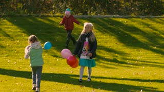 Funny little girls playing with colorful balloons on green meadow