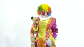 Funny young clown playing with puppet