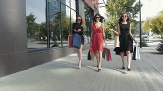 Group of attractive female friends walking in the city showing their purchases