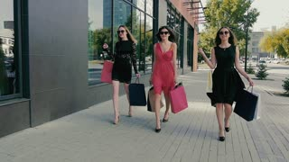 Group of attractive young women walking along shop windows. Slow motion