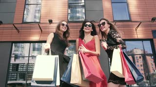 Group of cheerful women enjoying their successful shopping day in the city