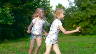 Group of children on a summer field having fun together and chasing each other