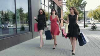 Group of lovely female friends walking down the street after a shopping day