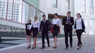 Group of stylish business people walking together down the street to their business center