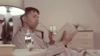 Handsome man wearing home clothes reading a book interestingly