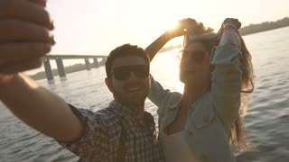 Happy couple in love taking selfie photo standing in front of a bright river