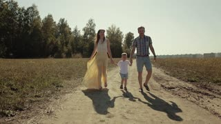 Happy family of three walking in the countryside together