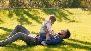 Happy father holding his little daughter in hands while lying on green grass