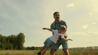 Happy father playing with his son picking him up in his arms. The boy imagines he flies like a plane