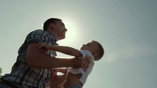 Happy father throws his son in the air and catches him. Sun rays shine brightly