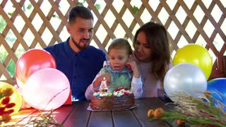 Happy little girl blowing out candle on her birthday cake and her loving parents kiss the her and clap the hands
