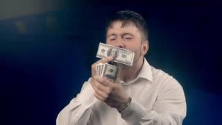 Happy man feels delight looking through a roll of bills