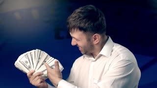 Happy man standing against blue background holding a fan of money and showing that it is cool