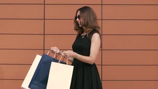 Happy shopping woman looking cheerfully into her shopping bag. Slow motion
