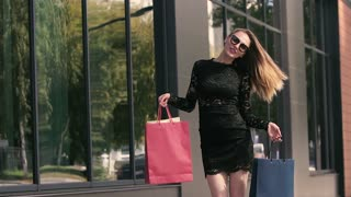 Happy smiling young woman cheerful in bliss enjoys her successful shopping