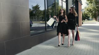 Happy young female friends walking together after shopping. Slow motion