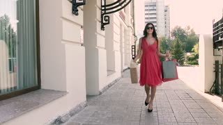 Happy young woman is walking down the street after shopping