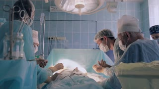 Hospital medical team wearing surgical clothing performing surgery using sterilized equipment