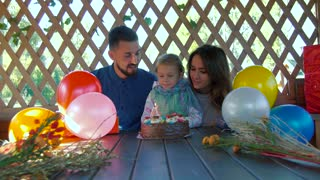 Humble little girl sitting with her parents and blowing out candles on her birthday cake