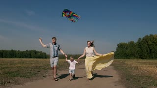 Joyful family flying a kite and running on the road with it