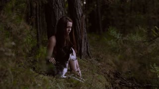 Likely girl sitting in nature with her wolf-looking dog