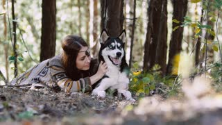 Likely young woman in the forest lying with beautiful dog and having fun