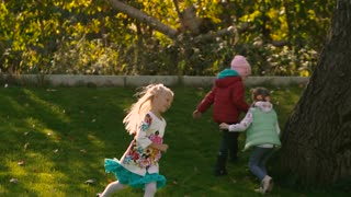 Little blond girl playing with other children on field