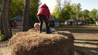 Little friendly girl helping another girl climb onto haystack and then jumping down
