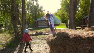 Little girls having fun in hay jumping and climbing on it