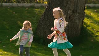 Little girls running in green park and enjoying their play