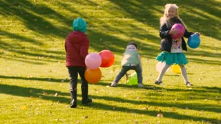 Little kids playing with balloons outdoors