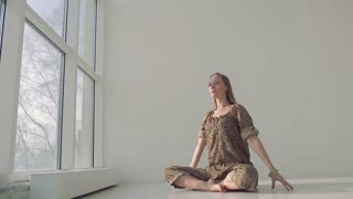 Lovely young woman bending to the side while practicing yoga